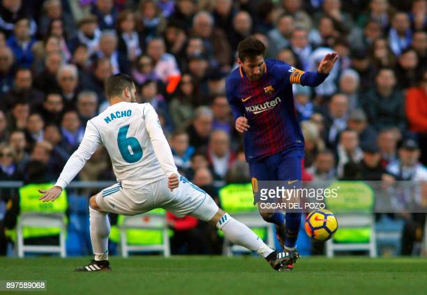 Real Madrid's Spanish defender Nacho Fernandez vies with Barcelona's Argentinian forward Lionel Messi during the Spanish League 'Clasico' football...
