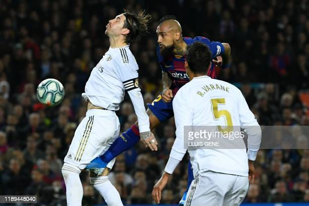 Real Madrid's Spanish defender Sergio Ramos and Barcelona's Chilean midfielder Arturo Vidal jump for the ball during the El Clasico Spanish League...