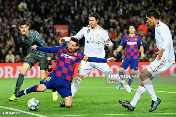 Real Madrid's Spanish defender Sergio Ramos and Real Madrid's French defender Raphael Varane challenge Barcelona's Argentine forward Lionel Messi...