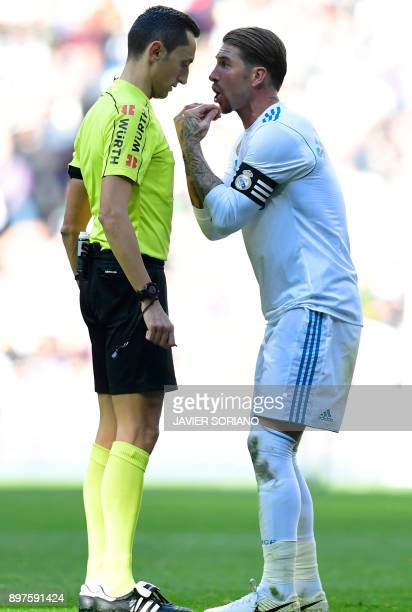 Real Madrid's Spanish defender Sergio Ramos argues with referee Jose Maria Sanchez Martinez during the Spanish League 'Clasico' football match Real...