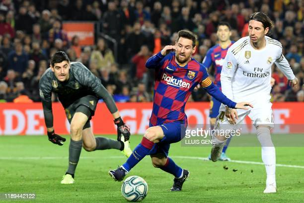 TOPSHOT Real Madrid's Spanish defender Sergio Ramos challenges Barcelona's Argentine forward Lionel Messi next to Real Madrid's Belgian goalkeeper...