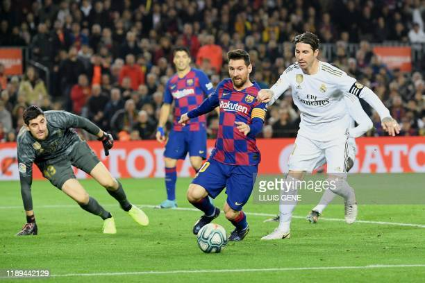 Real Madrid's Spanish defender Sergio Ramos challenges Barcelona's Argentine forward Lionel Messi next to Real Madrid's Belgian goalkeeper Thibaut...