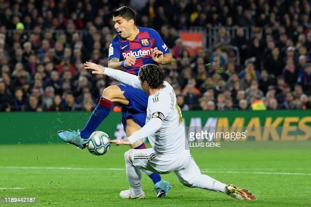 Real Madrid's Spanish defender Sergio Ramos challenges Barcelona's Uruguayan forward Luis Suarez during the El Clasico Spanish League football match...