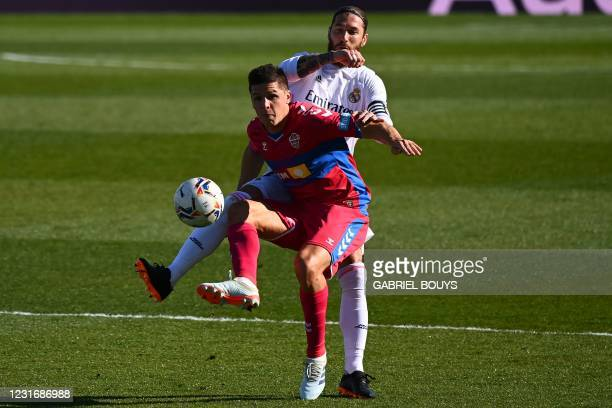 Real Madrid's Spanish defender Sergio Ramos challenges Elche's Argentinian forward Guido Carrillo during the Spanish League football match between...