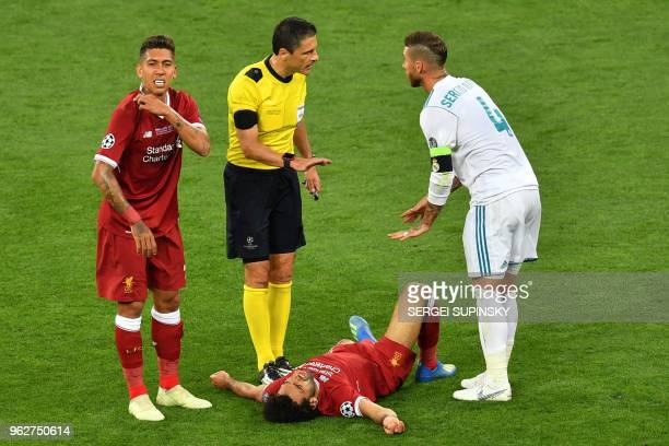 TOPSHOT Real Madrid's Spanish defender Sergio Ramos disusses with Serbian referee Milorad Mazic as Liverpool's Egyptian forward Mohamed Salah lays on...
