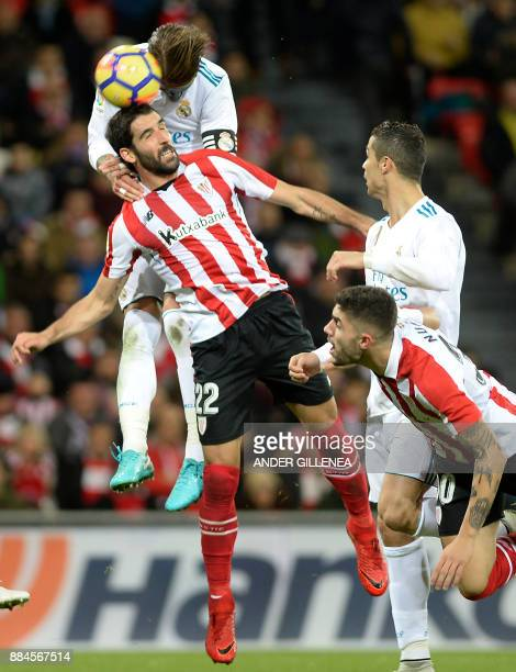 Real Madrid's Spanish defender Sergio Ramos heads the ball with Athletic Bilbao's Spanish midfielder Raul Garcia during the Spanish league football...