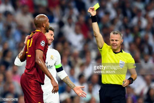 Real Madrid's Spanish defender Sergio Ramos is shown a yellow card by Dutch referee Bjorn Kuipers during the UEFA Champions League group G football...