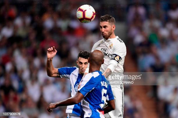 Real Madrid's Spanish defender Sergio Ramos jumps for the ball with Espanyol's Brazilian defender Naldo and Espanyol's Spanish defender Mario Hermoso...