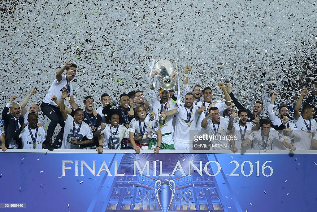TOPSHOT - Real Madrid's Spanish defender Sergio Ramos (C) lifts the trophy after Real Madrid won the UEFA Champions League final football match over Atletico Madrid at San Siro Stadium in Milan, on May 28, 2016. / AFP / OLIVIER