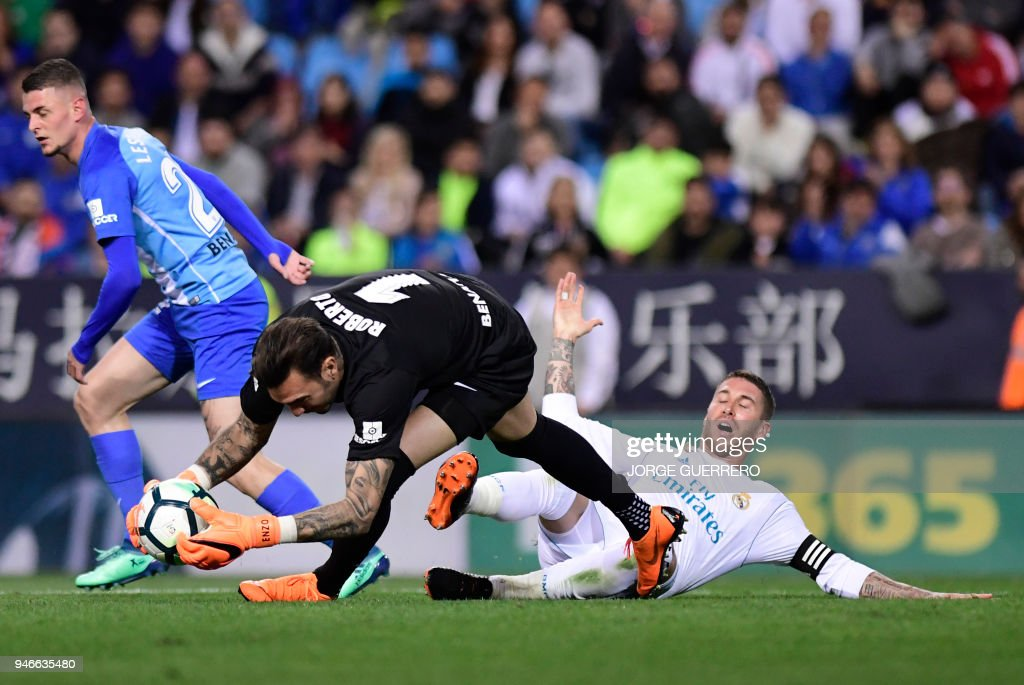 Real Madrid's Spanish defender Sergio Ramos (R) misses a goal opportunity as Malaga's Spanish goalkeeper Roberto (C) saves the ball beside Malaga's Belgian midfielder Maxime Lestienne (L) during the Spanish league footbal match between Malaga CF and Real Madrid CF at La Rosaleda stadium in Malaga on April 15, 2018. /