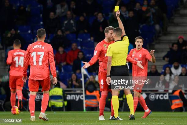 Real Madrid's Spanish defender Sergio Ramos reacts as he receives a yellow card from Spanish referee Jesus Gil Manzano during the Spanish league...