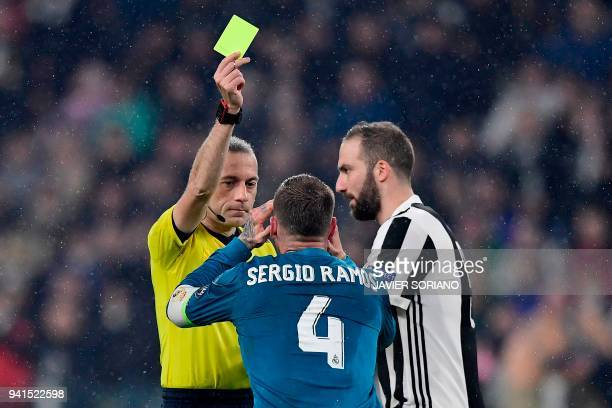 Real Madrid's Spanish defender Sergio Ramos reacts as he receives a yellow card by Turkish referee Cuneyt Cakir next to Juventus' Argentinian forward...