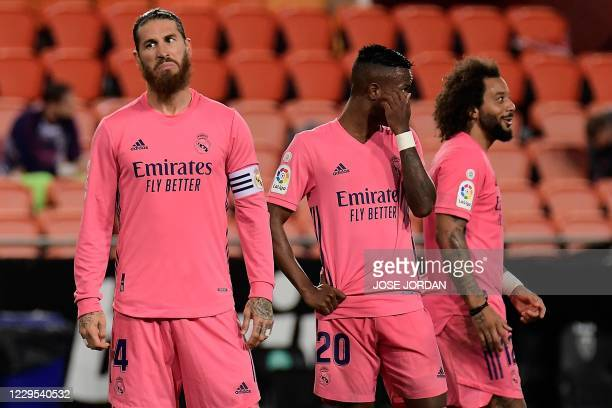 Real Madrid's Spanish defender Sergio Ramos reacts next to Real Madrid's Brazilian defender Marcelo and Real Madrid's Brazilian forward Vinicius...