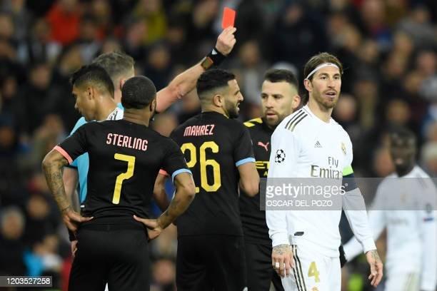 Real Madrid's Spanish defender Sergio Ramos receives a red card from Italian referee Daniele Orsato during the UEFA Champions League round of 16...