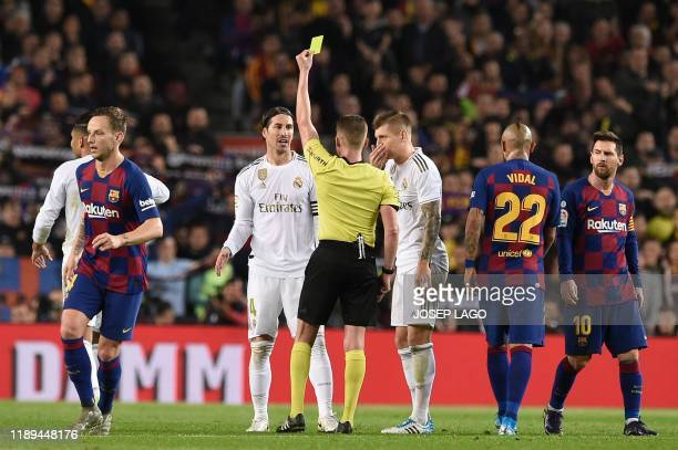 Real Madrid's Spanish defender Sergio Ramos receives a yellow card by the referee during the El Clasico Spanish League football match between...