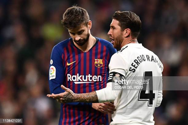 Real Madrid's Spanish defender Sergio Ramos talks with Barcelona's Spanish defender Gerard Pique during the Spanish league football match between...