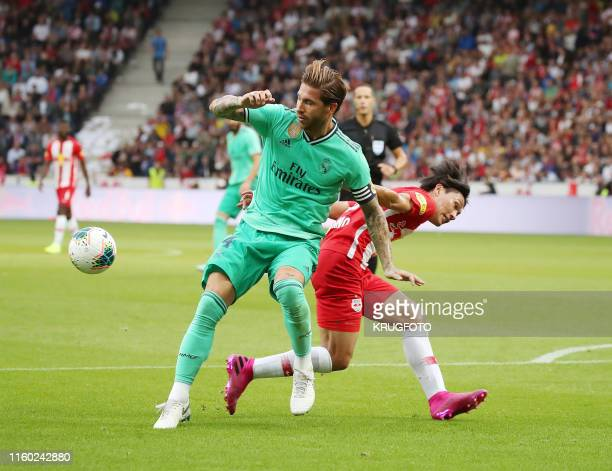 Real Madrid's Spanish defender Sergio Ramos vies for the ball Red Bull Salzburg's Japanese forward Takumi Minamino during the pre-Season friendly...