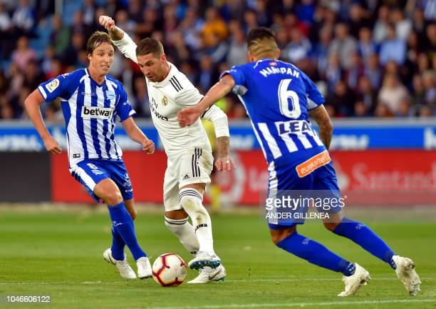 Real Madrid's Spanish defender Sergio Ramos vies with Alaves' Spanish midfielder Pina and Chilean defender Guillermo Maripan during the Spanish...