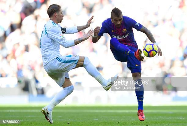 Real Madrid's Spanish defender Sergio Ramos vies with Barcelona's Brazilian midfielder Paulinho during the Spanish League 'Clasico' football match...