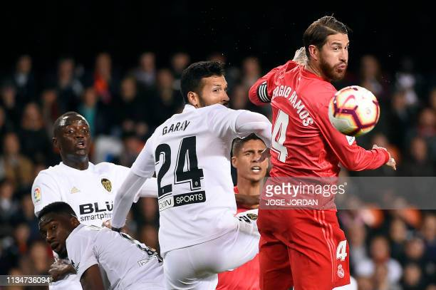 Real Madrid's Spanish defender Sergio Ramos vies with Valencia's Argentinian defender Ezequiel Garay during the Spanish league football match between...