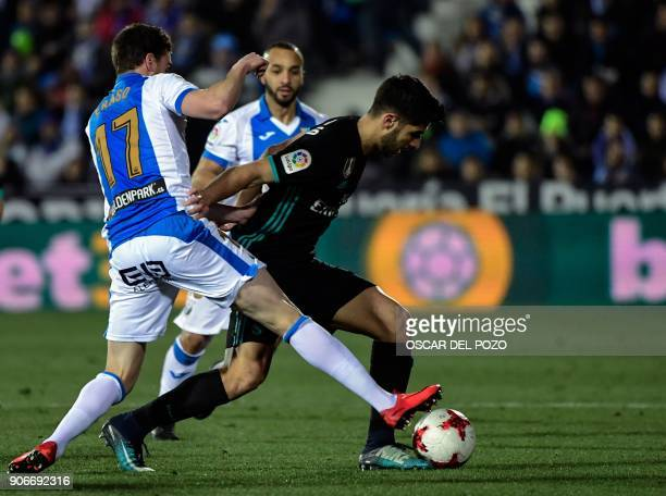 Real Madrid's Spanish forward Marco Asensio challenges Leganes' defender Javier Eraso during the Spanish 'Copa del Rey' football match between...