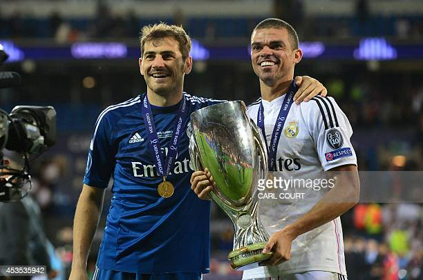 Real Madrids Spanish goalkeeper Iker Casillas and Real Madrids Portuguese defender Pepe celebrate with the trophy on the pitch after the UEFA Super...