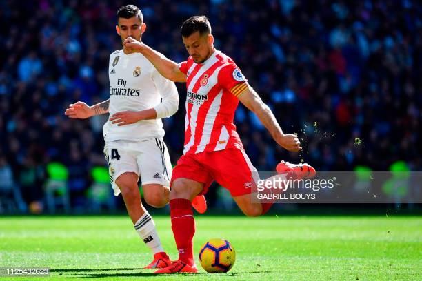 Real Madrid's Spanish midfielder Daniel Ceballos challenges Girona's Spanish midfielder Alex Granell during the Spanish League football match between...