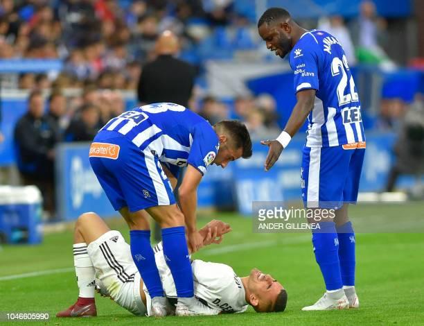 Real Madrid's Spanish midfielder Daniel Ceballos lies on the ground between Alaves' Spanish midfielder Jony and Ghanaian forward Wakaso Mubarak...