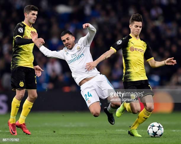 Real Madrid's Spanish midfielder Daniel Ceballos vies with Dortmund's German midfielder Julian Weigl and Dortmund's US midfielder Christian Pulisic...