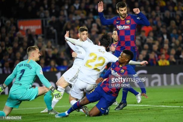 Real Madrid's Spanish midfielder Isco and Real Madrid's Uruguayan midfielder Federico Valverde challenge Barcelona's German goalkeeper MarcAndre Ter...