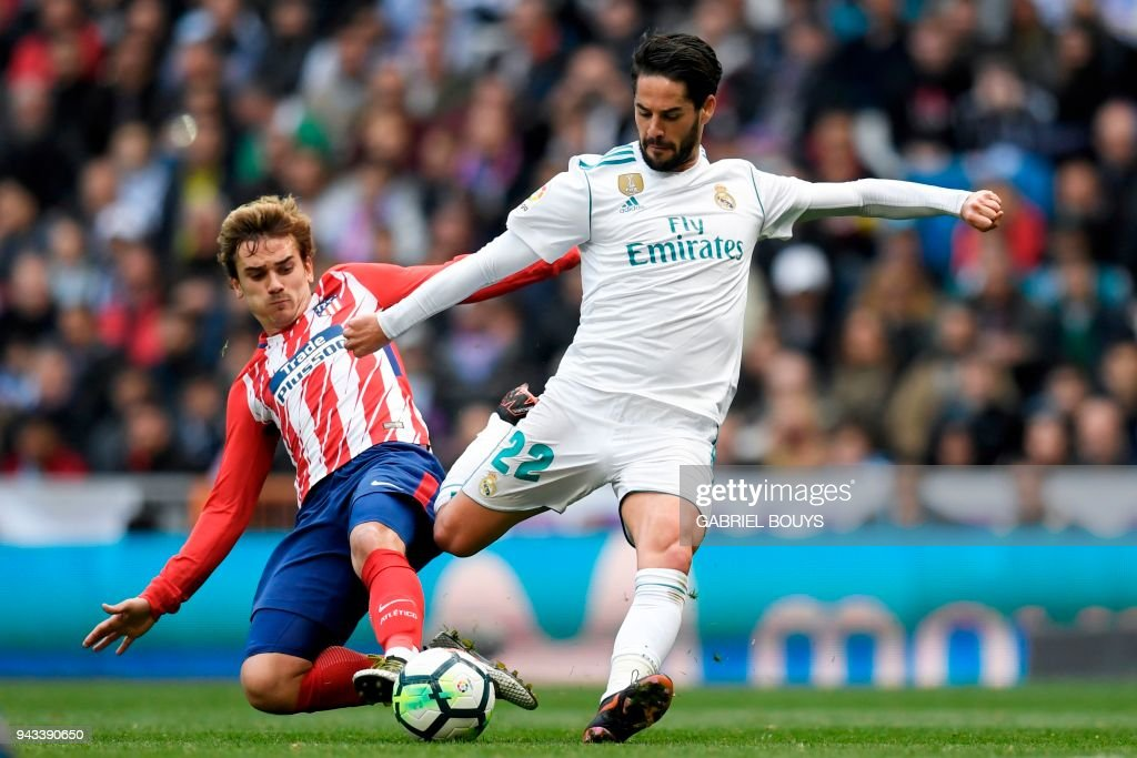 TOPSHOT - Real Madrid's Spanish midfielder Isco (R) challenges Atletico Madrid's French forward Antoine Griezmann during the Spanish league football match between Real Madrid CF and Club Atletico de Madrid at the Santiago Bernabeu stadium in Madrid on April 8, 2018. /