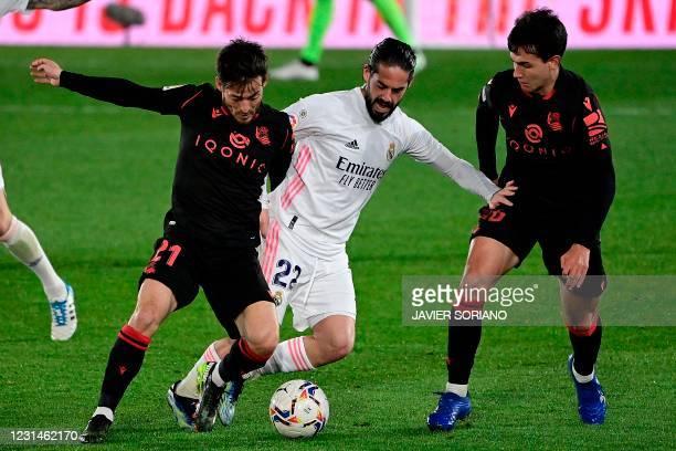 Real Madrid's Spanish midfielder Isco challenges Real Sociedad's Spanish midfielder David Silva and Real Sociedad's Spanish midfielder Martin...