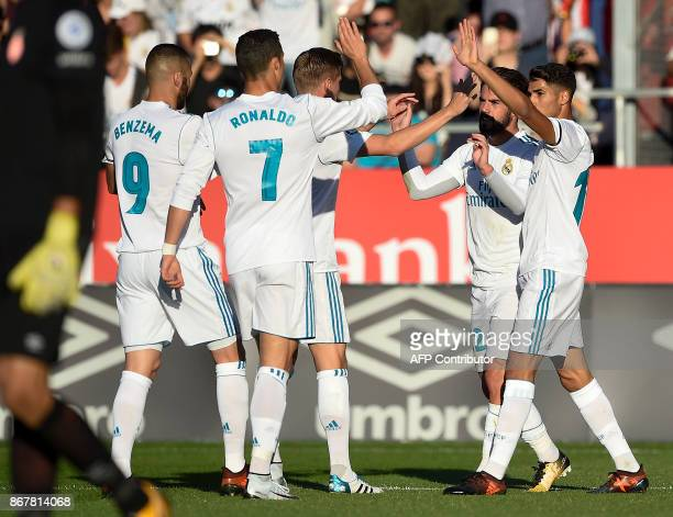 Real Madrid's Spanish midfielder Isco is congratulated by teammates after scoring a goal during the Spanish league football match Girona FC vs Real...