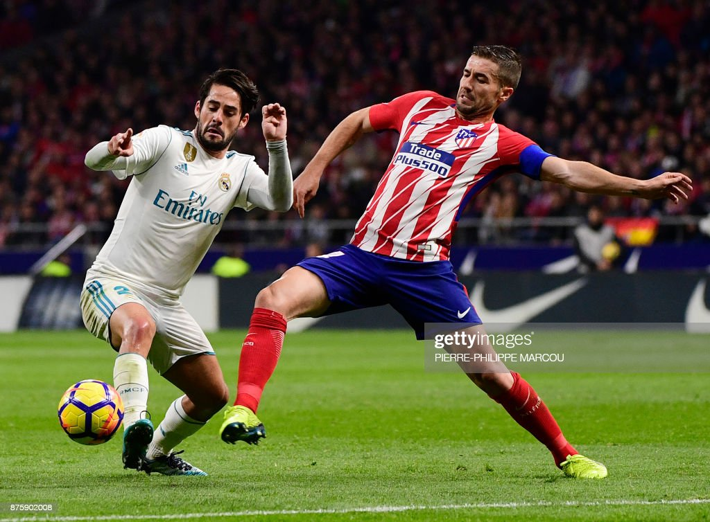 Real Madrid's Spanish midfielder Isco (L) vies with Atletico Madrid's Spanish midfielder Gabi during the Spanish league football match Atletico Madrid vs Real Madrid at the Wanda Metropolitan stadium in Madrid on November 18, 2017. /