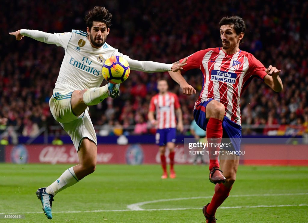 Real Madrid's Spanish midfielder Isco (L) vies with Atletico Madrid's Montenegrin defender Stefan Savic during the Spanish league football match Atletico Madrid vs Real Madrid at the Wanda Metropolitan stadium in Madrid on November 18, 2017. /