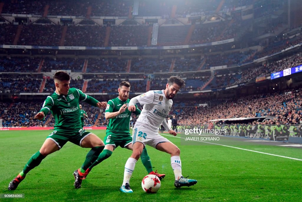 TOPSHOT - Real Madrid's Spanish midfielder Isco (R) vies with Leganes' Spanish defender Tito (C) and Leganes' Spanish defender Unai Bustinza during the Spanish 'Copa del Rey' (King's cup) quarter-final second leg football match between Real Madrid CF and CD Leganes at the Santiago Bernabeu stadium in Madrid on January 24, 2018. /