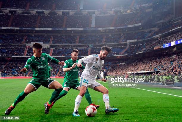 TOPSHOT Real Madrid's Spanish midfielder Isco vies with Leganes' Spanish defender Tito and Leganes' Spanish defender Unai Bustinza during the Spanish...