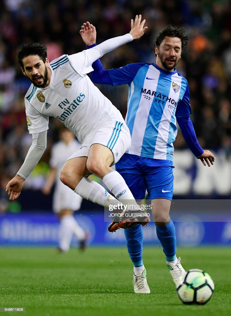 Real Madrid's Spanish midfielder Isco (L) vies withy Malaga's Chilean midfielder Manuel Iturra during the Spanish league footbal match between Malaga CF and Real Madrid CF at La Rosaleda stadium in Malaga on April 15, 2018. /