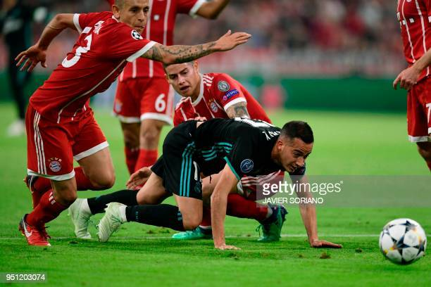 Real Madrid's Spanish midfielder Lucas Vazquez vies with Bayern Munich's Brazilian defender Rafinha and Bayern Munich's Colombian midfielder James...