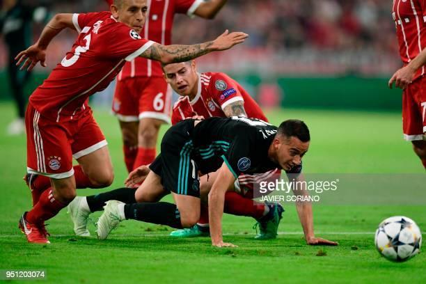 Real Madrid's Spanish midfielder Lucas Vazquez vies with Bayern Munich's Brazilian defender Rafinha and Bayern Munich's Colombian midfielder James...
