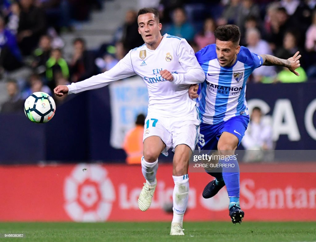 Real Madrid's Spanish midfielder Lucas Vazquez (L) vies with Malaga's Spanish defender Ivan Rodriguez during the Spanish league footbal match between Malaga CF and Real Madrid CF at La Rosaleda stadium in Malaga on April 15, 2018. /