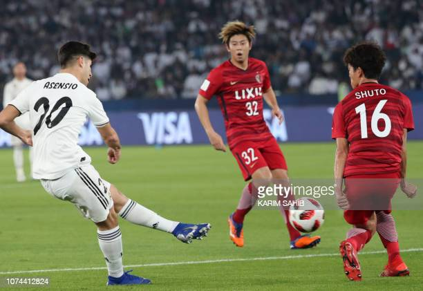 Real Madrid's Spanish midfielder Marco Asensio attempts a shot as he is marked by Kashima Antler's defender Shuto Yamamoto during the semi final...