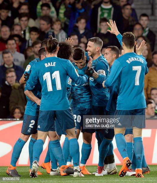 Real Madrid's Spanish midfielder Marco Asensio celebrates scoring a goal with teammates during the Spanish league football match Real Betis vs Real...