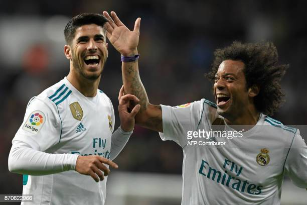 Real Madrid's Spanish midfielder Marco Asensio celebrates with Real Madrid's Brazilian defender Marcelo after scoring a goal during the Spanish...