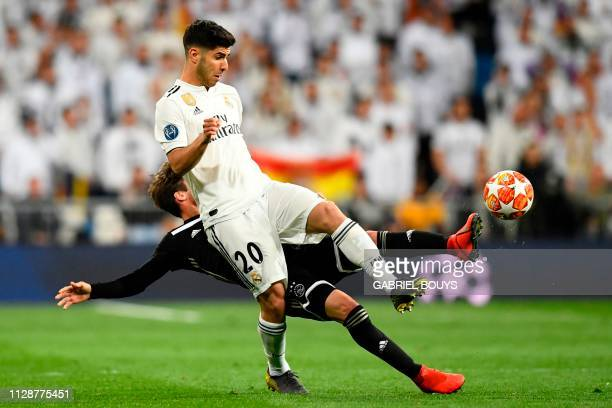Real Madrid's Spanish midfielder Marco Asensio challenges Ajax's Argentinian defender Nicolas Tagliafico during the UEFA Champions League round of 16...