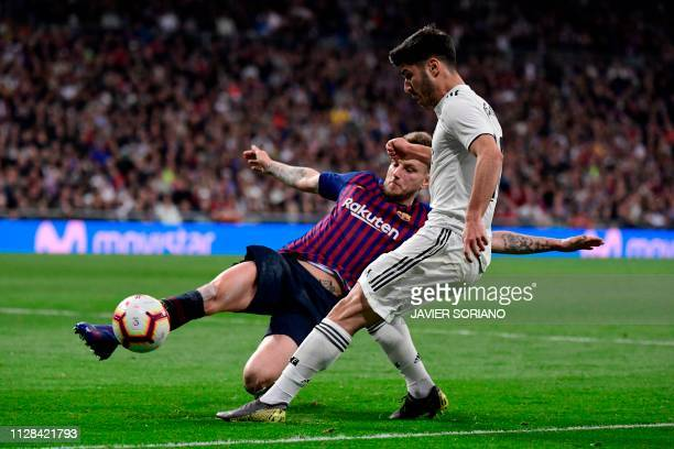Real Madrid's Spanish midfielder Marco Asensio challenges Barcelona's Croatian midfielder Ivan Rakitic during the Spanish league football match...