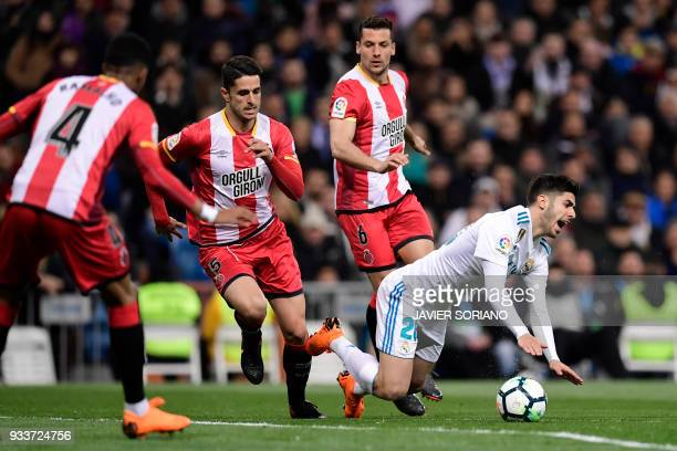 Real Madrid's Spanish midfielder Marco Asensio falls down beside Girona's Spanish defender Pedro Alcala and Girona's Spanish defender Pedro Alcala...