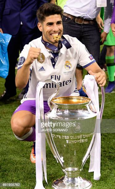 Real Madrid's Spanish midfielder Marco Asensio poses with the trophy after Real Madrid won the UEFA Champions League final football match between...