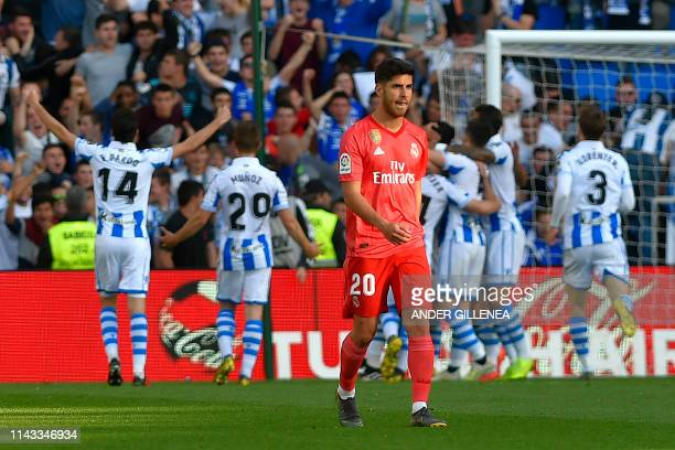 Real Madrid's Spanish midfielder Marco Asensio reacts as Real Sociedad's players celebrate after scoring a goal during the Spanish League football...