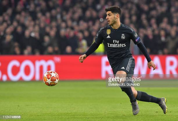 Real Madrid's Spanish midfielder Marco Asensio runs with the ball during the UEFA Champions league round of 16 first leg football match between Ajax...